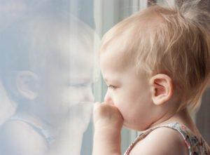 窓の外を見つめる子供